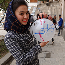 a young woman holds a white balloon with writing on it