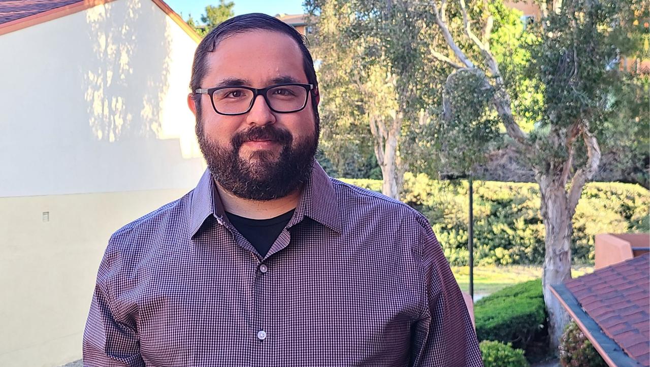 Ricardo Ceballos stands outdoors smiling