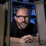 Jonathan Alexander sits at a desk looking towards the camera between two stacks of books