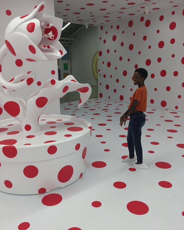 Samantha Carter wearing orange shirt and jeans in artsy room with white walls and big red polka dots-