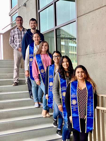 The first graduating class of the Spanish/English bilingual education minor standing on a staircase smiling with Julio Torres