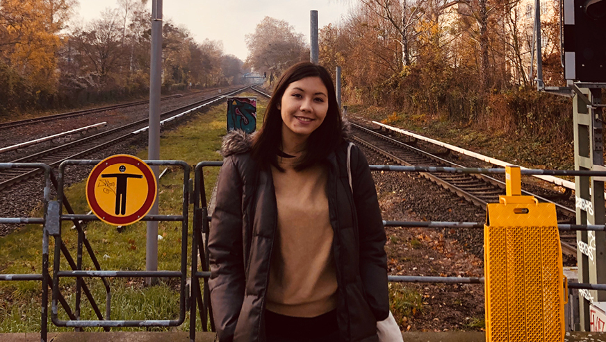 Zoe Portnoff stands between two train tracks smiling