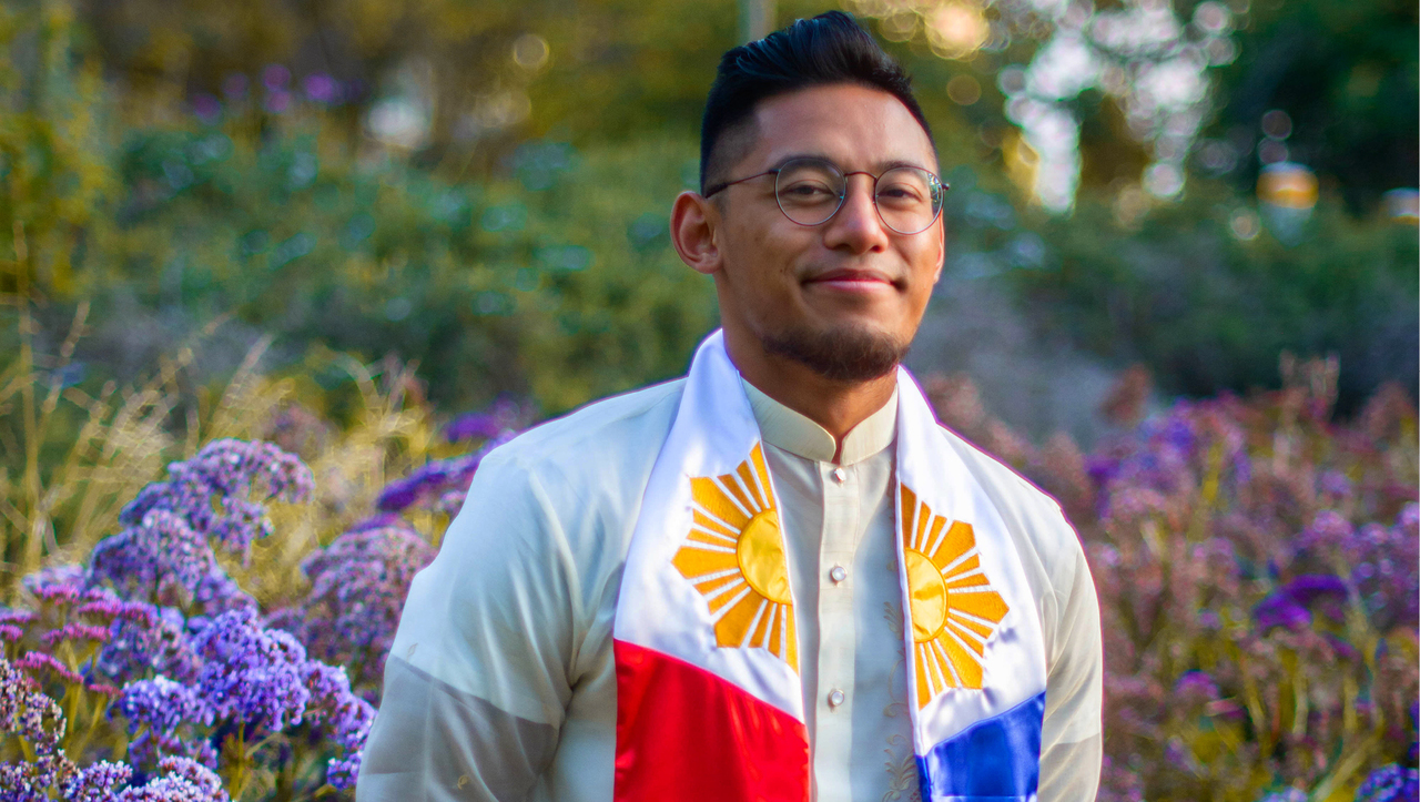 Manny De Leon smiles in a field of flowers