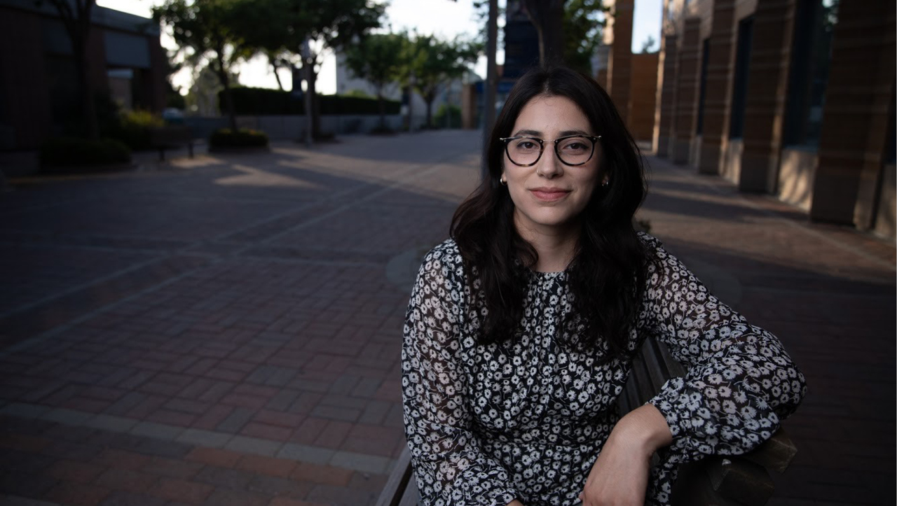 Paulina Guajardo sits on a bench outside of Humanities Gateway