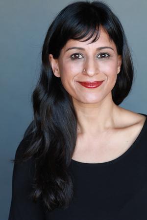 Dr. Sunita Puri smiling with red lips long black shiny hair long-sleeved black top