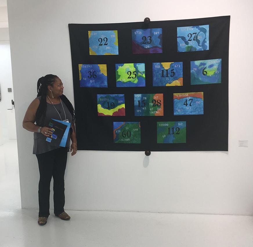 Kathie Foley-Meyer stands next to her artwork,