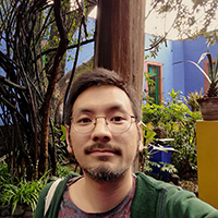 A selfie of André Keiji Kunigami in a garden in front of a blue home
