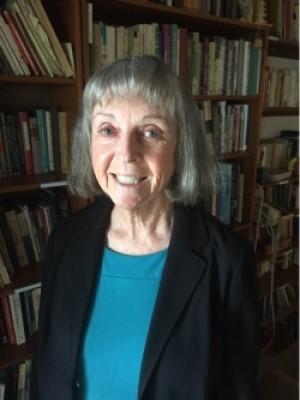 Dr.JohannaShapiro_in_teal_shirt_and_navy_blazer_in_front_of_bookshelf