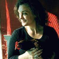 Brianne Donaldson looking to the left holding a chicken with red background