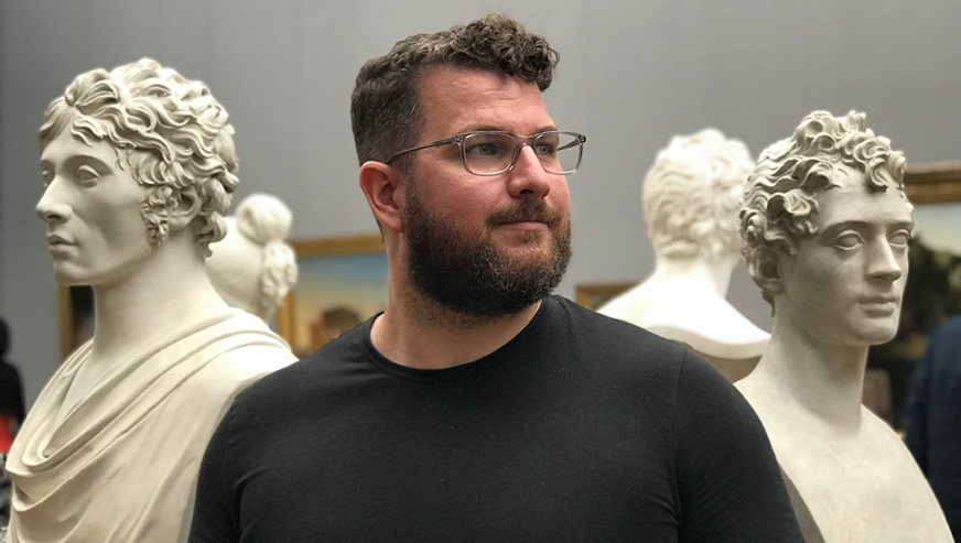 James Bliss stands between two marble statues looking to his left