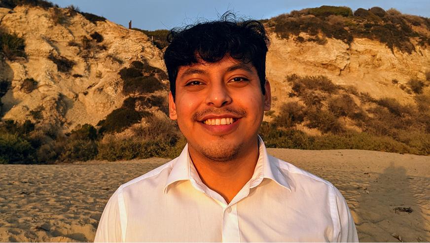 Orbelin Portillo Blancas stands on the beach smiling