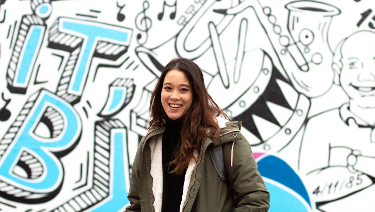 Ingrid Allen smiles in front of a wall with street art on it