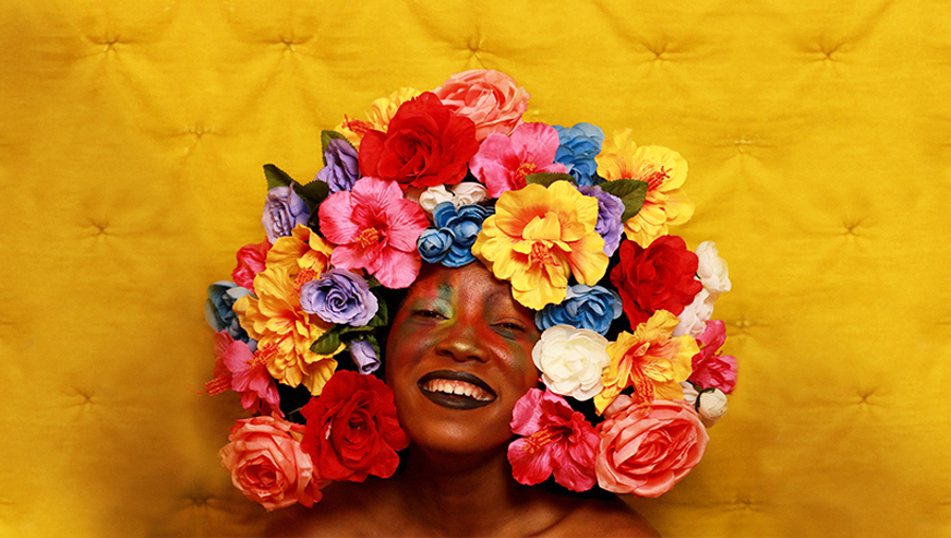 Arielle Sidney wears a crown of flowers and smiles in front of a yellow background