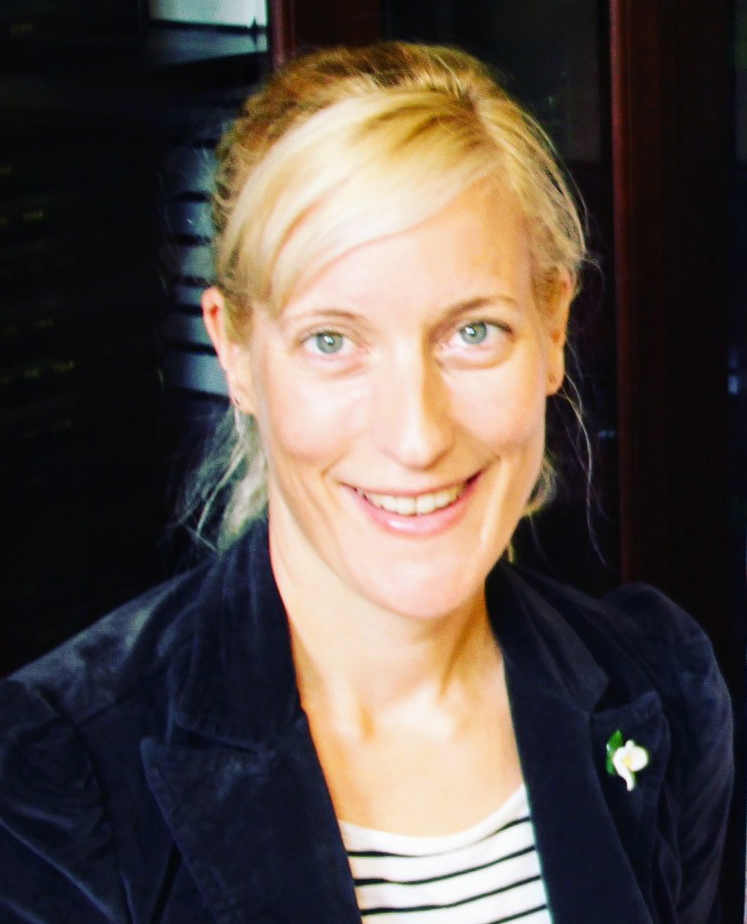 Dr. Kathrin Herrmann smiling blonde hair pulled back blue striped shirt blue blazer