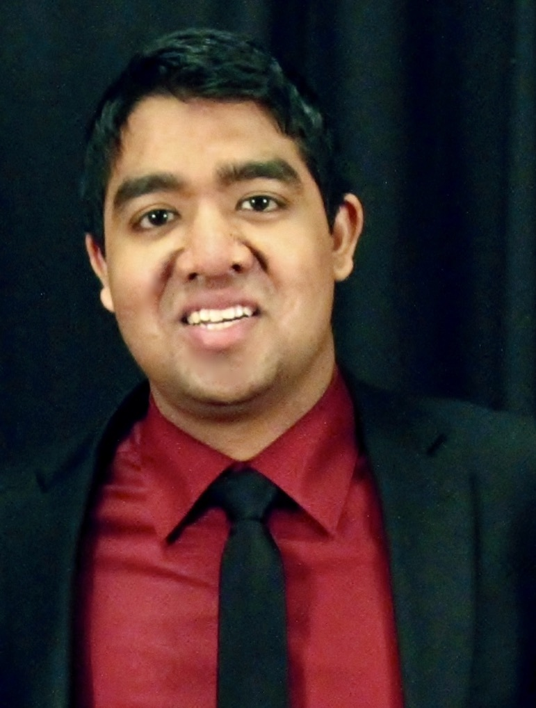Kunal Parikh smiling wearing suit and tie with black draped background