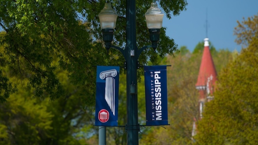 Light pole on campus with the University of Mississippi Flags hanging